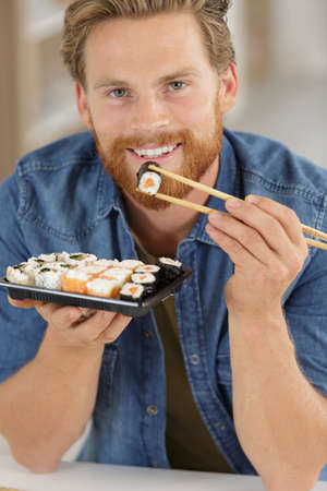 man holding sushi with chopsticks
