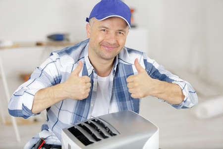 hvac worker with ventilation system equipment showing thumbs-up