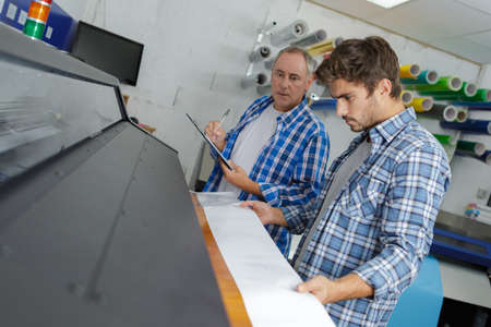 two men looking down at professional printer