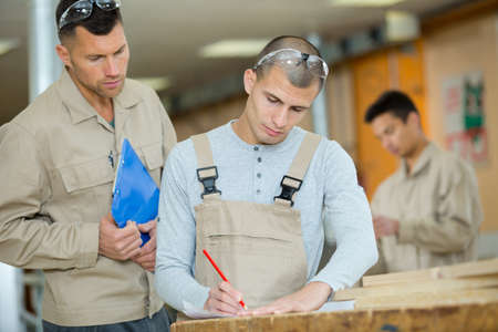carpenter supervising student in woodwork class