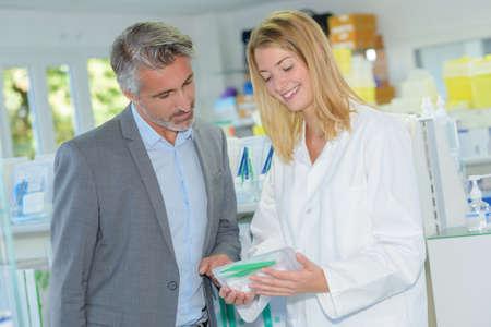 female pharmacist advising male customer