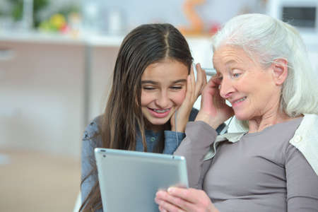 Grandmother looking at tablet with granddaughter Banco de Imagens