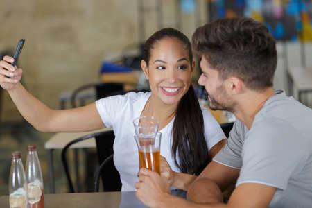 couple in love taking selfie at beer bar