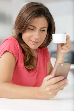 young woman with coffee cup using phone
