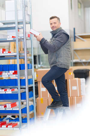 worker taking a product on the top Stock Photo