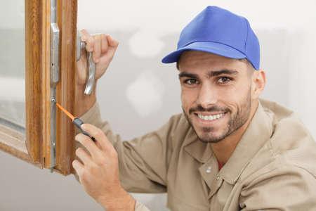 portrait of male window fitter using screwdriver