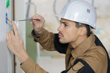 he is installing electricity socket Stock Photo