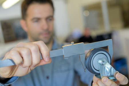men measures a wheel with calliper