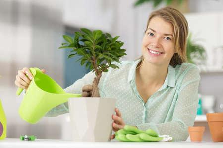 woman happy watering bonsai