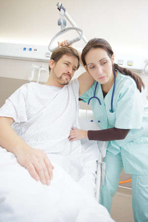 nurse helps sick male patient out of bed