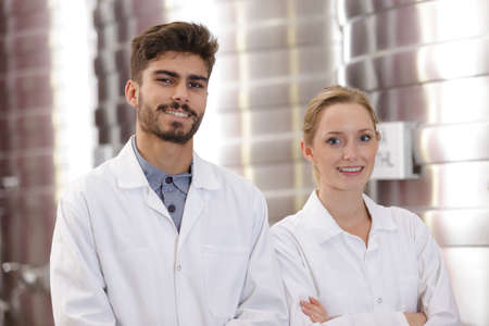 man and woman in lab coats working in a factory
