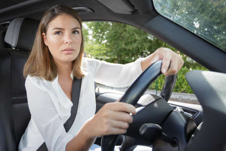 serious woman driving car looking through the window