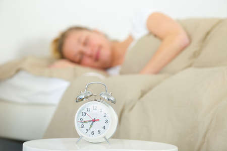 attractive woman sleeping with the alarm clock