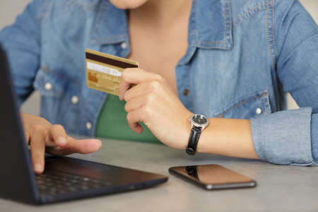 woman buying online payment on laptop reading credit card number Banco de Imagens