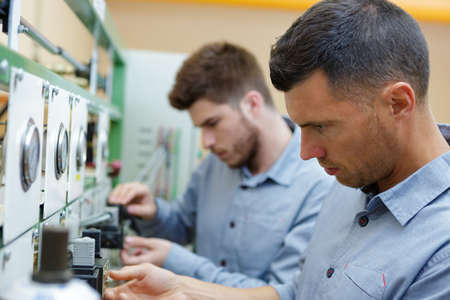 two male technicians working on electrical panel with dials