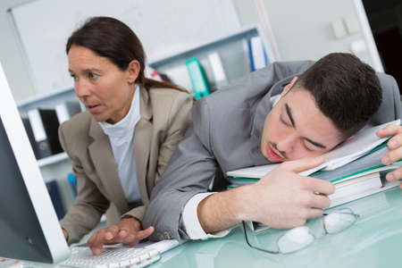 female manager next to a sleeping office worker
