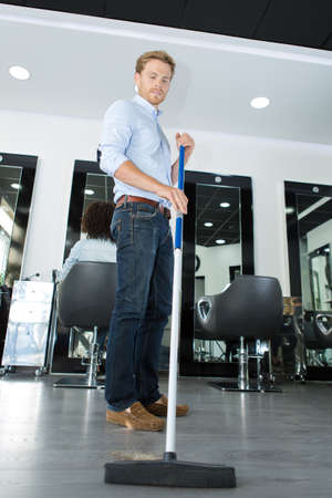 man sweeping up hair from hairdressing salon floor