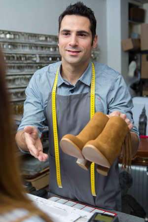 cobbler giving boots to female customer Stock Photo