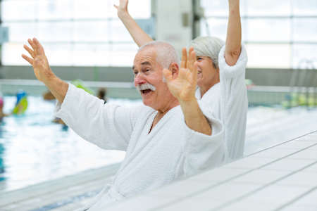 senior couple waving in a swimming pool
