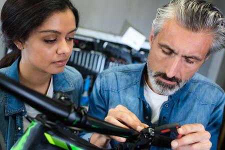 positive guy and girl hiring bikes ot rental store Banco de Imagens