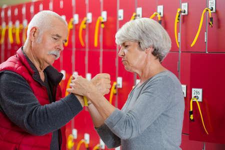 senior couple attaching locker bracelet in leisure center changing room
