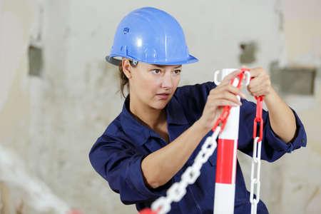 female builder putting up safety barrier around work site Banque d'images