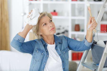 independent mature woman decorating apartment