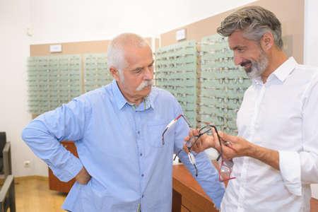 male pensioner choosing glasses at the optics store