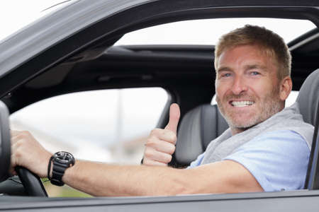 middle-aged male driver holding thumbs up through car window 版權商用圖片