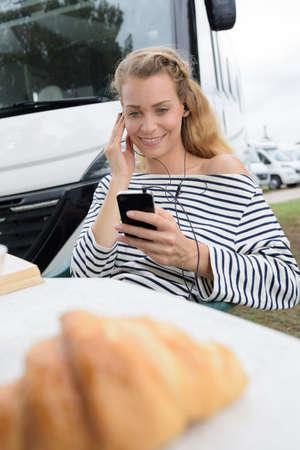 woman sits near their camper van having breakfast