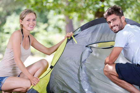 couple of travelers putting cover on tent they assemble