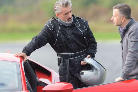 man talking to racing driver
