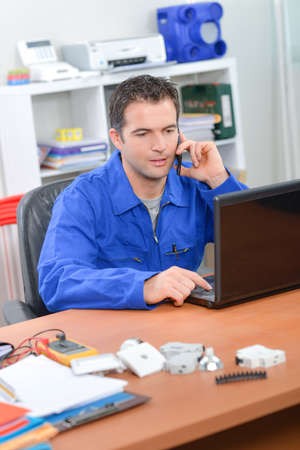 Electrician working at his desk Foto de archivo