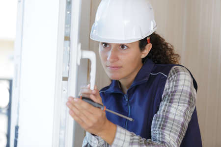 woman builder working using a screwdriver and fix the door