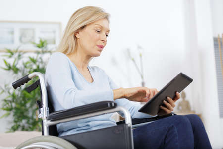 happy mature woman in wheelchair using interent assistance