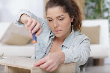 a woman screwing a furniture Stock fotó