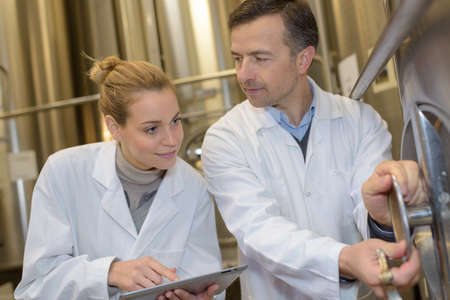 positive worker assembly line operator working in modern wine factory Banque d'images