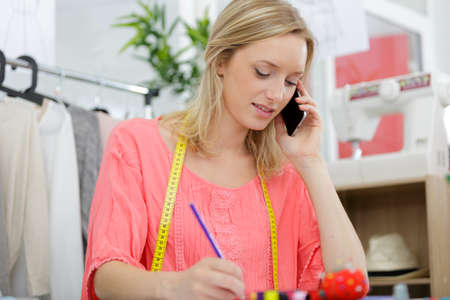 dressmaker talking on cellphone while writing