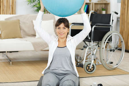 woman in wheelchair is doing sport with ball