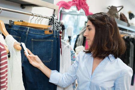 woman looking at clothing price tag