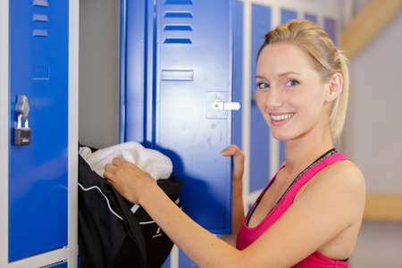 blonde woman by the locker-room in the gym Stock Photo