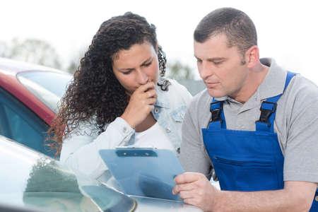 male mechanic and female customer outdoors