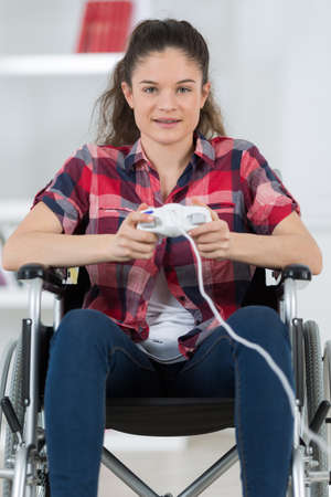 girl in wheelchair holding computer joystick