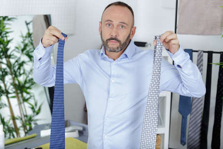 man chooses necktie at home Stock Photo