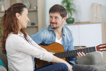 romantic couple at home playing guitar on the sofa