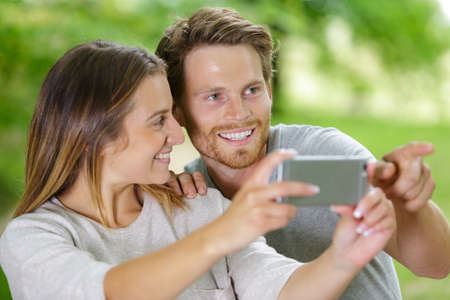 couple clicking selfie with smart phone in forest