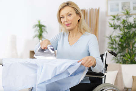 mature woman sitting on wheelchair and ironing