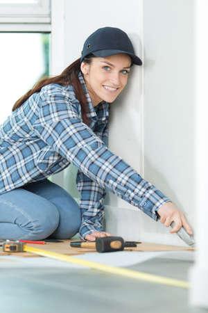 a handywoman cutting wooden floor
