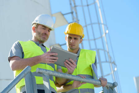 workers in charge of silo looking at tablet Standard-Bild