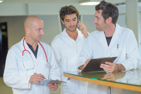 three male doctors holding clipboards conferring together